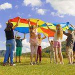 Nens i nenes juguen amb un paracaigudes de colors