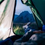Imatge d'alguna persona estirada a l'interior d'una tenda de campanya, des d'on es veu el paisatge de l'entorn