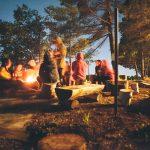 Imatge de nois i noies al voltant d'un foc, en un campament d'estiu